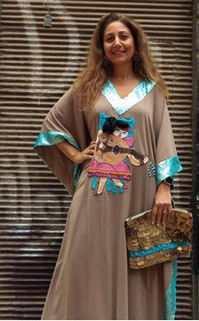 "Picture of Make a cultural statement in our ""Badee3a"" abaya! Hand embroidered aqua sequins complements the neutral tones. Complete the look with the golden coin clutch with embedded clusters of turquoise stones."