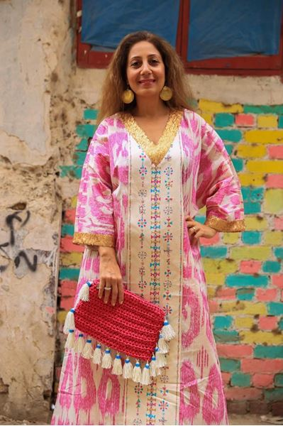 """Picture of Wanna dress to impress? Our """"Siwa"""" galabeya promises to do just that!!! It's all about the perfect marriage of color and pattern. The look is perfect with our Fuchsia clutch"""